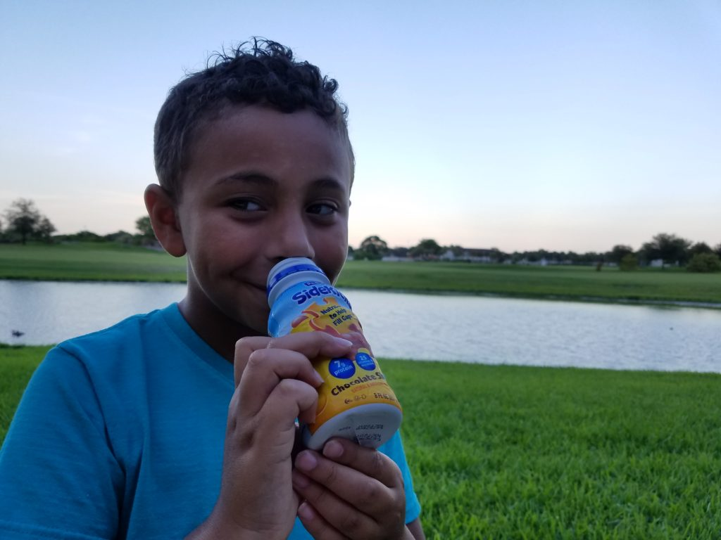 son drinking Pediasure Sidekicks outside