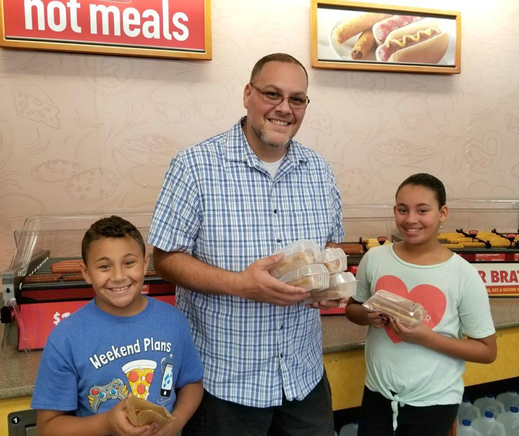 Family holding RaceTrac Hotdogs