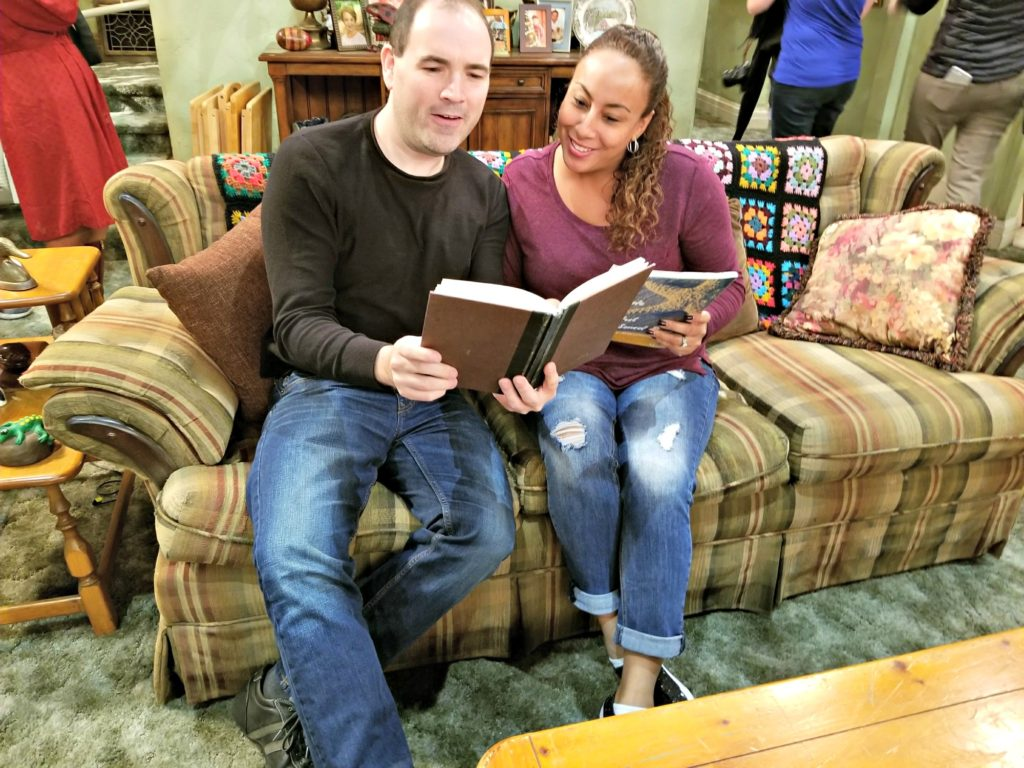 Reading a book on the couch on Roseanne set