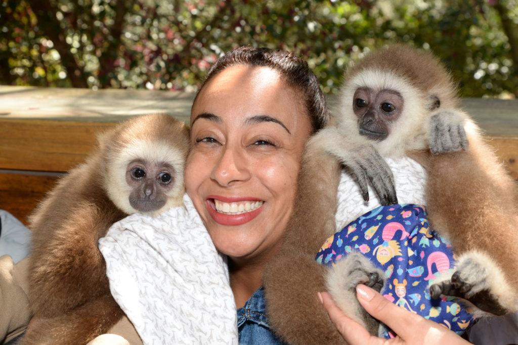 woman with 2 gibbon monkeys