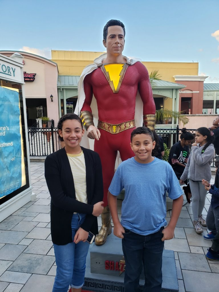 Kids in front of a Shazam statue