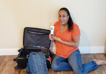 Woman holding toothpaste next to a suit case