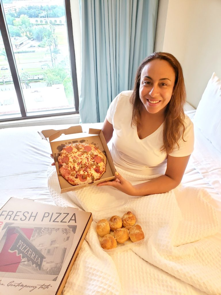 Lady eating pizza on a hotel bed