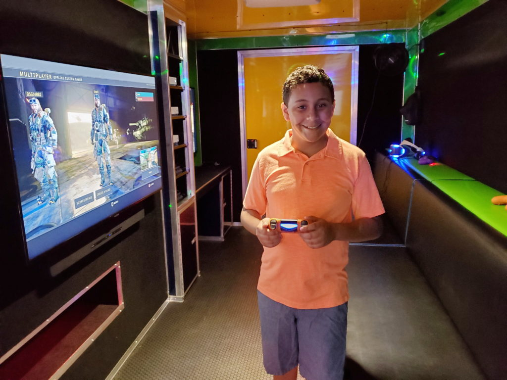 boy playing video game inside game truck