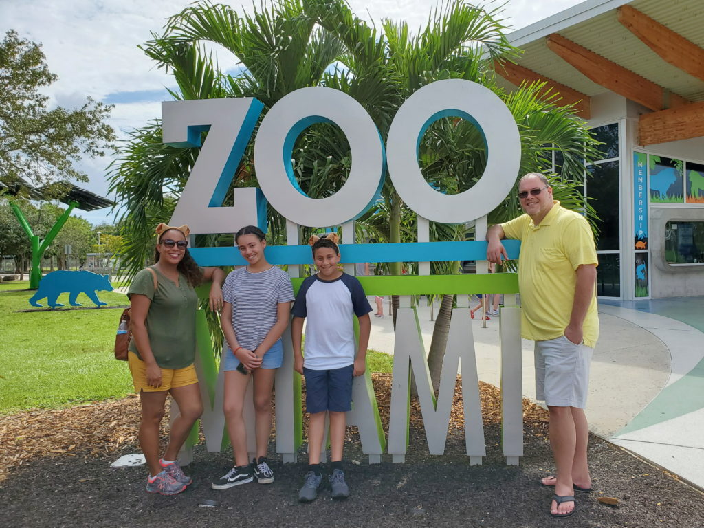family in front of the Zoo Miami Sign