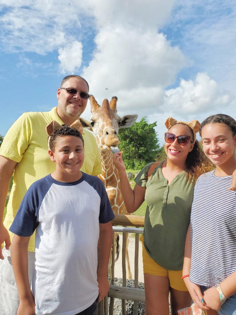 family feeding a giraffe