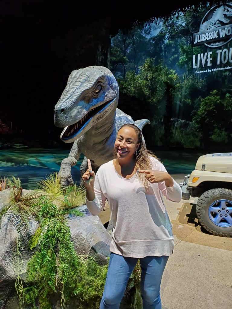 lady posing with a dinosaur