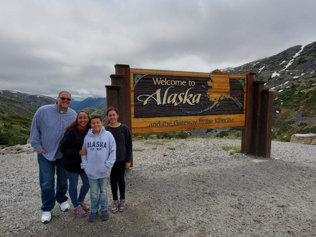 Family in front of Alaska sign